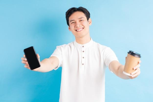 Ein foto eines gutaussehenden asiatischen mannes, der sein telefon und pappbecher in seiner hand hält