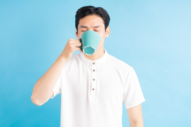 Ein foto eines gutaussehenden asiatischen mannes, der von einer blauen tasse trinkt