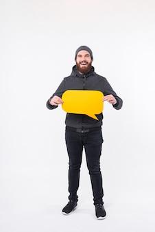 Ein foto eines mannes, der eine sprechblase hält und aufgeregt ist, schaut nahe einer weißen wand