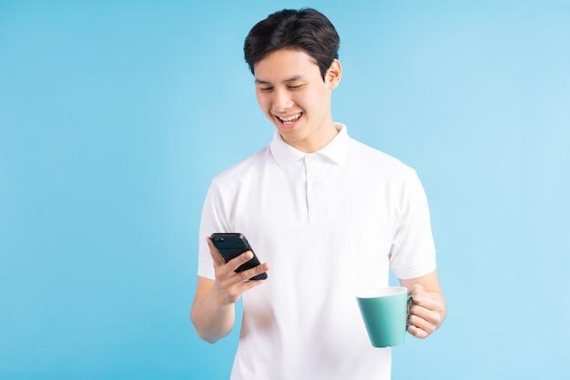 Ein foto eines schönen asiatischen mannes, der während des trinkwassers eine sms sendet