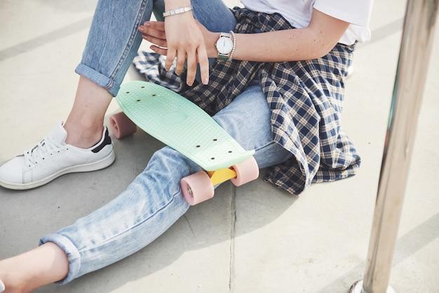 Ein foto eines schönen mädchens mit schönen haaren hält ein skateboard auf einem langen brett