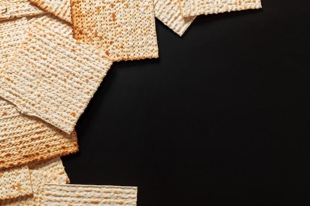 Ein foto von matzah- oder matzastücken auf schwarzem. matzah für die jüdischen passahfeiertage. platz für text, kopieren sie platz