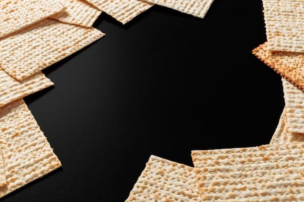 Ein foto von matzah- oder matzostücken auf schwarzem. matzah für die jüdischen passahfeiertage.