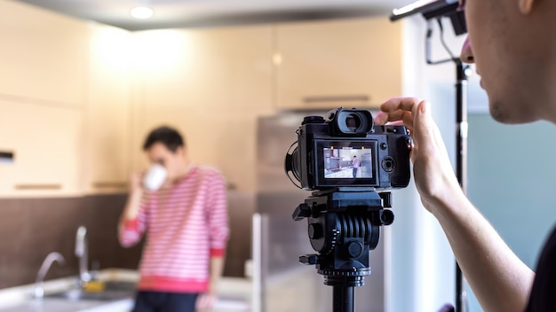 Ein fotograf, der einen mann erschießt, der auf der küche trinkt