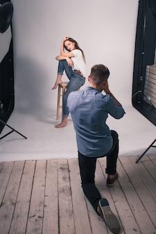 Ein fotograf fotografiert ein mädchenmodel in einem studio