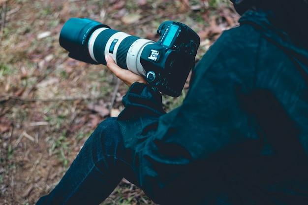 Ein fotograf hält eine kamera, bereitet ein foto von verschiedenen aufgaben vor