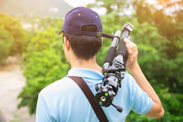 Ein fotograf oder ein reisender mit einem kamerastativ in der natur für hintergrund.