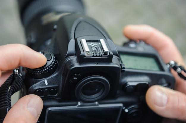 Ein fotograf stellt die kamera ein.