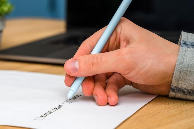 Ein fragebogen mit antwortmöglichkeiten für das feedback-formular. ein mann klickt ein kästchen auf einem weißen papier an