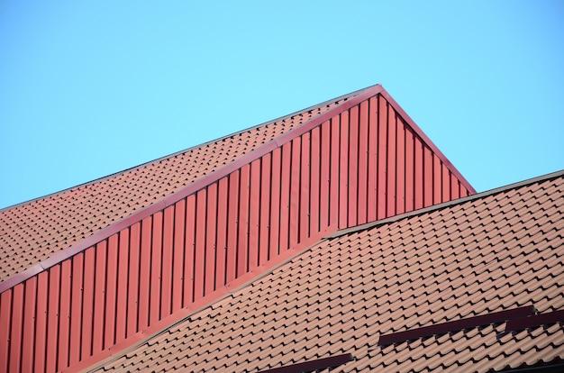 Ein fragment eines dachs aus einer metallfliese von dunkelroter farbe. qualität dachdecker
