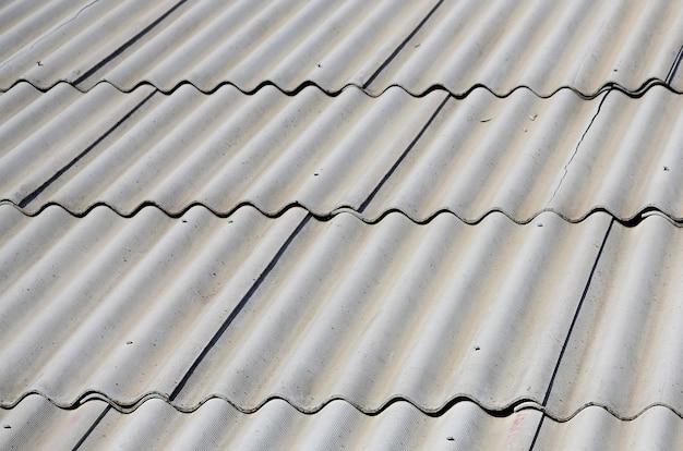 Ein fragment eines grauen schieferdachs einer alten probe aus asbestmaterial
