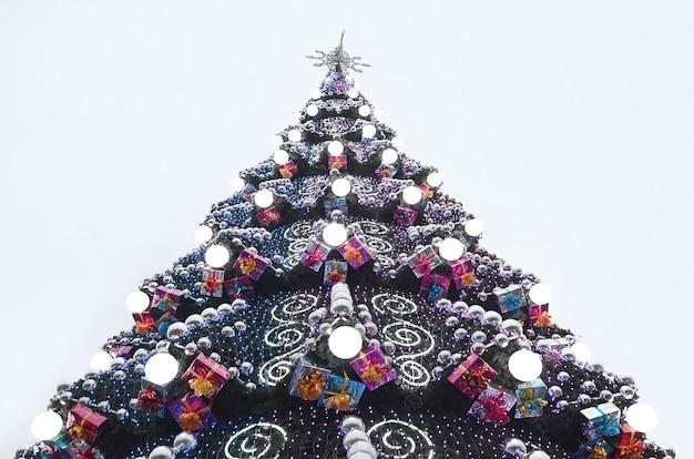 Ein fragment eines riesigen weihnachtsbaumes mit vielen ornamenten, geschenkboxen und leuchtenden lampen
