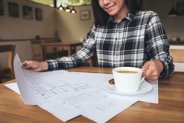 Ein frauenarchitekt, der an geschäftszeichnungspapier beim trinken des kaffees im büro arbeitet