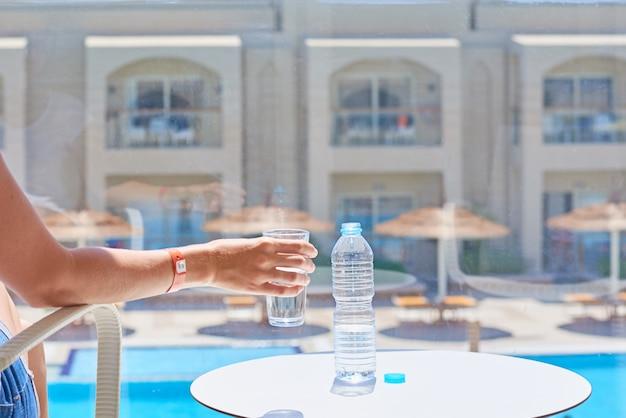 Ein frauenhandgriffglas wasser am hotelbalkon gegen swimmingpool