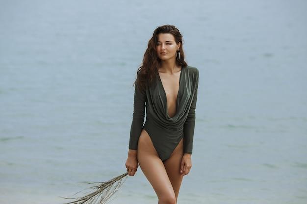 Ein frauenmodell, das einen modischen badeanzug trägt, palmblatt hält und gegen meer steht