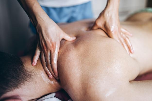 Ein frauenphysiotherapeut, der rückenmassage für einen mann im ärztlichen dienst tut
