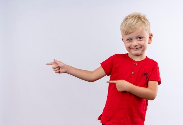 Ein freudiger kleiner süßer blonder junge im roten t-shirt, der mit zeigefingern zeigt, während er auf eine weiße wand schaut