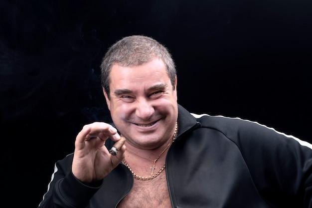 Ein freundlicher, aufrichtig lachender weißer dicker mann, der eine zigarre raucht. aufrichtige gefühle. ein gutmütiger erwachsener mann, ein porträt auf schwarzem hintergrund