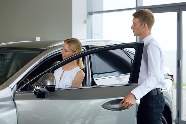 Ein freundlicher autohändler erklärt im autohaus die vor- und nachteile eines neuwagens