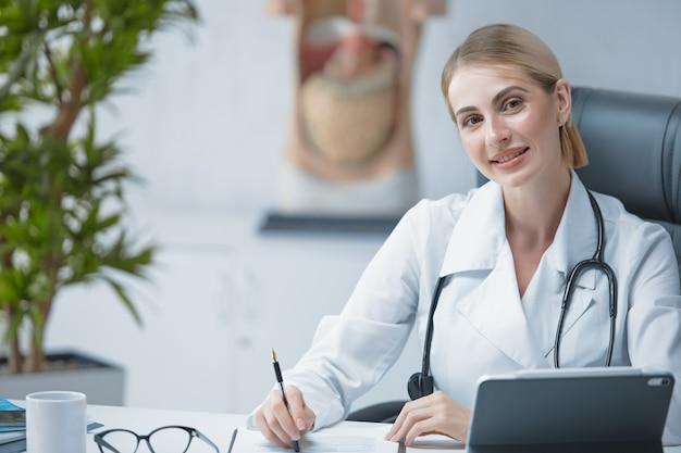 Ein freundlicher junger facharzt mit stethoskop um den hals an einem schreibtisch in einem hellen büro