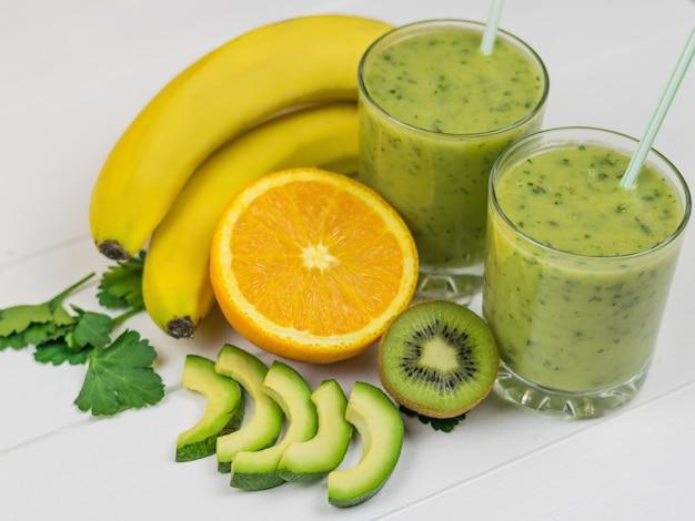 Ein frisch zubereiteter smoothie aus avocado, banane, petersilie, zitrone, orange und kiwi auf einem rustikalen holztisch