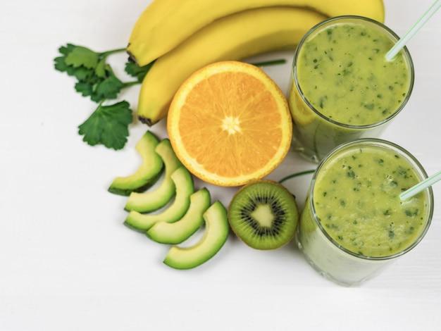Ein frisch zubereiteter smoothie aus avocado, banane, petersilie, zitrone und kiwi auf einem weißen holztisch