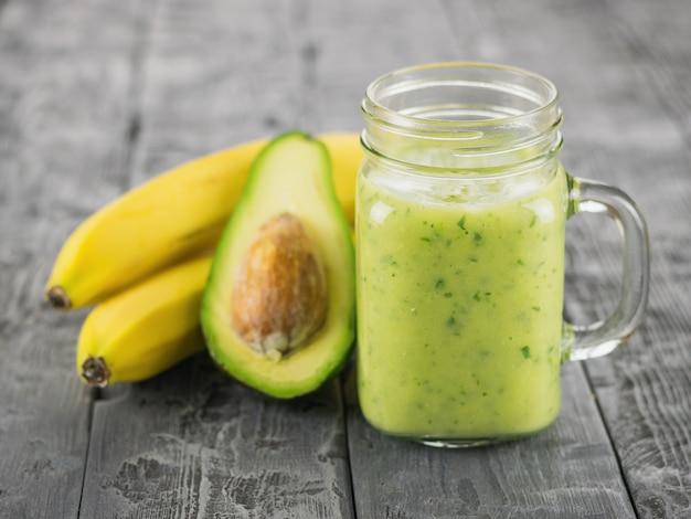 Ein frisch zubereiteter smoothie der avocado, der banane, der orange, der zitrone, der petersilie und der kiwi auf einem holztisch. diät vegetarisches essen.