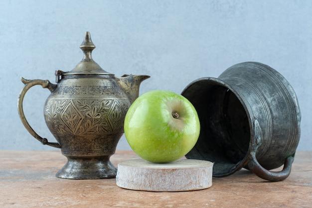 Ein frischer apfel mit einer alten tasse auf marmortisch.