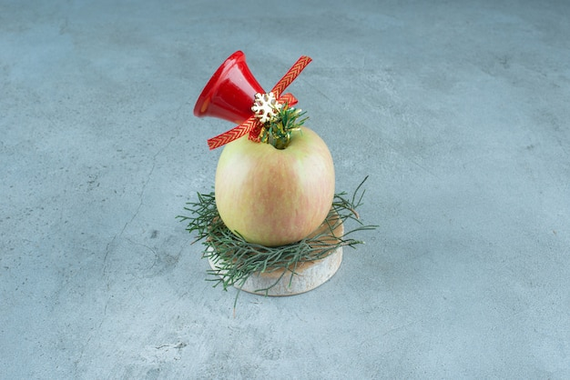 Ein frischer apfel mit roter weihnachtsglocke auf marmor.