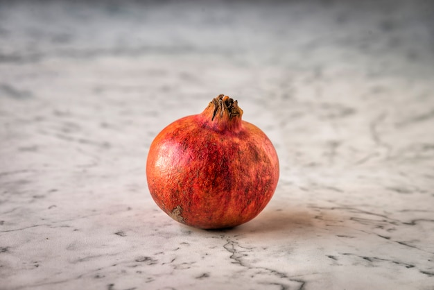 Ein frischer granatapfel auf einer marmoroberfläche