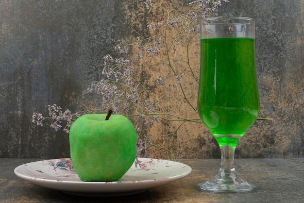 Ein frischer grüner apfel mit glas grünem wasser auf dunklem teller.
