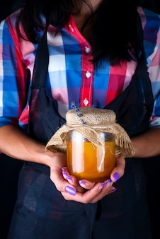 Ein frischer organischer honig in einem glas einer frau hält in den händen auf einem dunklen hintergrund. gesundes essen