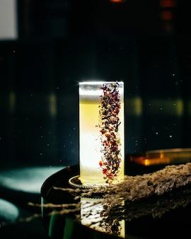 Ein frischer und gefrorener eiscocktail von vorne in einem langen glas auf der dunklen, dunklen oberfläche mit einer cocktailbar mit getränkesaft