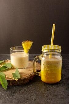 Ein frisches cocktail-leckeres kühlendes getränk der vorderansicht innerhalb der dose mit strohhalm nahe holzschreibtisch entlang grüner blätter auf dem dunklen hintergrund trinken sommersaft