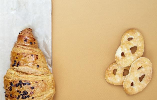 Ein frisches knuspriges croissant mit schokoladenfüllung und keksen auf braunem oder kaffeehintergrund mit kopienraum. klassisches traditionelles frisch gebackenes französisches dessert, gebäck. ansicht von oben, flach.