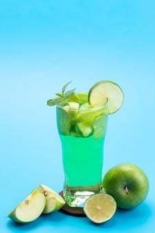 Ein frischobstcocktail von vorne mit frischen fruchtscheiben, die auf blauem eis eiskalt sind, trinken saftcocktailfruchtfarbe