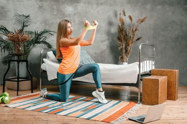Ein fröhlicher athlet mit blonden haaren stürzt sich mit online-training ins schlafzimmer.
