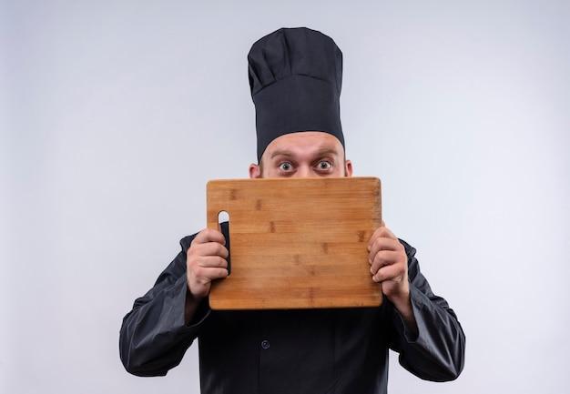 Ein fröhlicher bärtiger kochmann in der schwarzen uniform, die lächelnd zeigt und hölzerne küchenbrett auf einer weißen wand zeigt