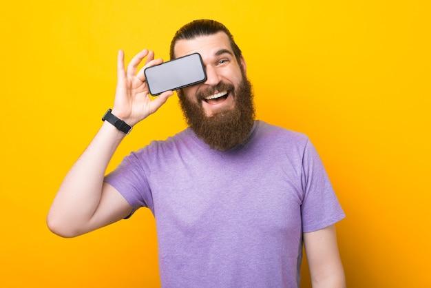 Ein fröhlicher bärtiger mann hält ein smartphone in der nähe seines auges und lächelt in die kamera