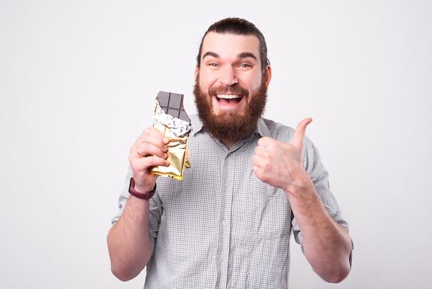 Ein fröhlicher bärtiger mann hält eine schokolade in der hand und lächelt in die kamera, zeigt einen daumen nach oben und dass er die schokolade liebt