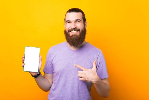 Ein fröhlicher bärtiger mann hält einen pc und lächelt in die kamera zeigt darauf