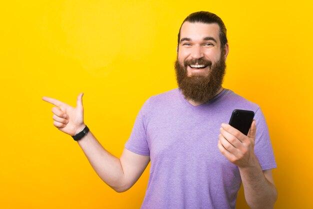 Ein fröhlicher bärtiger mann lächelt in die kamera, die sein telefon hält und auf einen freien platz zeigt