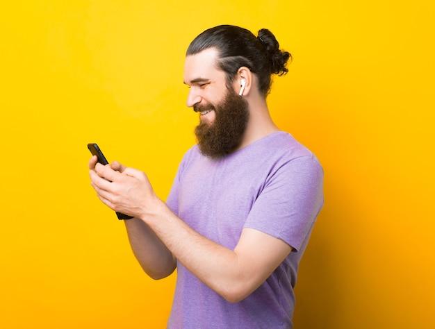 Ein fröhlicher bärtiger mann tippt auf seinem telefon eine nachricht, während er die musik in den ohrstöpseln hört.