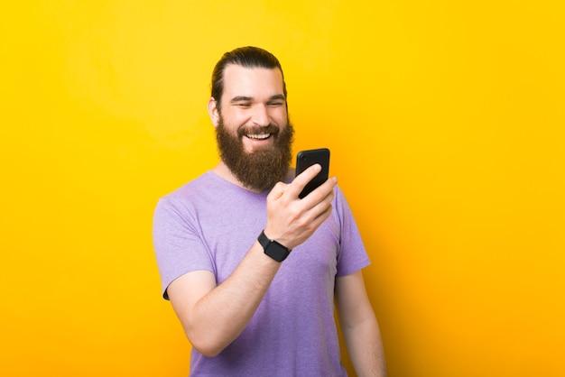 Ein fröhlicher bärtiger mann unterhält sich glücklich mit jemandem auf seinem neuen smartphone