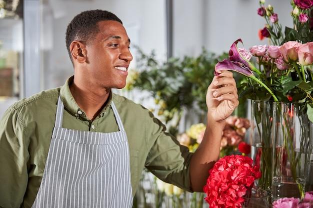 Ein fröhlicher blumenkünstler, der eine schürze mit streifen trägt, während er den zustand einer lila blume untersucht examining