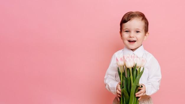 Ein fröhlicher gentleman hält einen strauß zarter rosa tulpen in den händen. platz für ihren text, platz kopieren