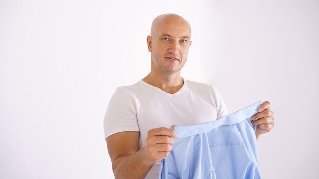 Ein fröhlicher glatzkopf in einem weißen t-shirt schaut nach dem waschen auf ein blaues hemd. das konzept des waschens und reinigens von wäsche