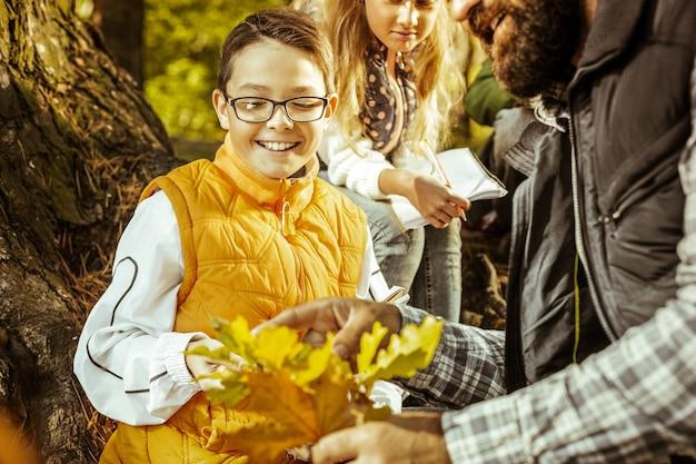 Ein fröhlicher junge in brille und orangefarbener weste, der an einem schönen tag die blätter seines lehrers betrachtet