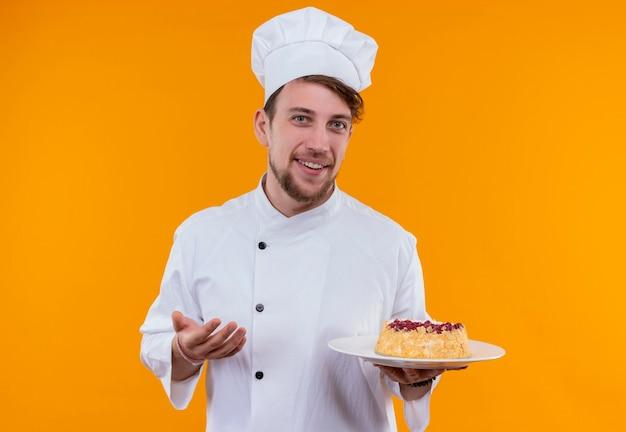 Ein fröhlicher junger bärtiger kochmann, der weiße kochuniform und einen hut trägt, der einen teller mit kuchen zeigt, während er auf eine orange wand schaut