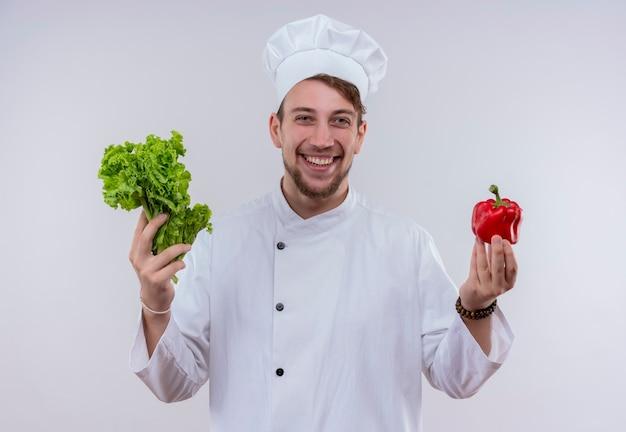 Ein fröhlicher junger bärtiger kochmann, der weiße kochuniform und hut hält, der grünen blattsalat und roten paprika hält, während auf einer weißen wand schaut